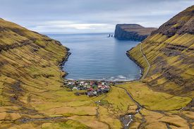Aerial view over the village of Tjornuvik with the sea stacks Risin and Kellingin (the giant and the wtich) in the distance off the northern coast of  the island of Eysturoy in the Faroe Islands.