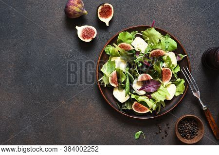 Mix Salad With Figs And Brie Cheese On A Concrete Background