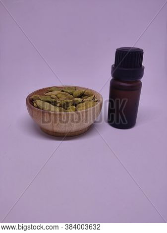 A Bottle Of Essential Oil With Whole Cardamon Seeds In A Traditional Spice Pot.