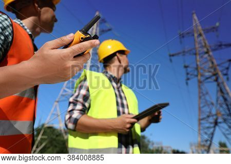 Professional Electricians Near High Voltage Towers, Focus On Hand With Portable Radio Station