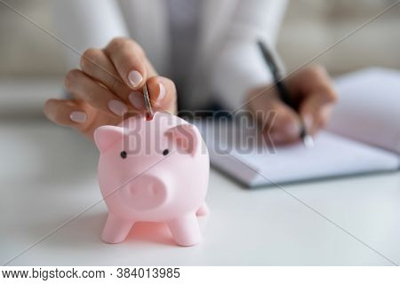 Close Up Young Female Hands Putting Coin In Piggybank.