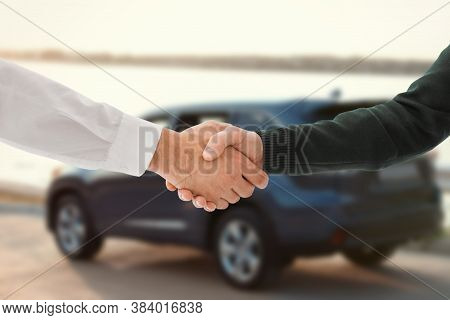 Man Buying Car And Shaking Hands With Salesman Against Blurred Auto, Closeup