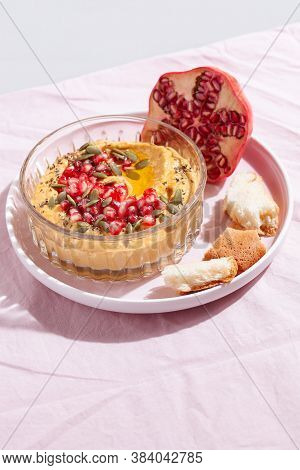 Pumpkin Hummus Dip With Pomegranate And Seed Topping On Pink Textile Background. Healthy Thanksgivin