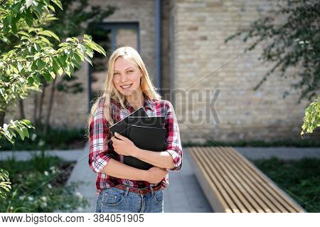 Happy Adult High School Student Standing Near Campus Building, Smiling Wide, Hugging Copybooks With
