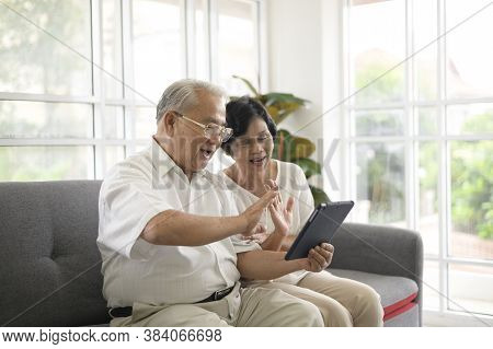 An Asian Happy Seniors Elderly Are Video Calling , Relax At Home, Smiling Healthy Senior Retired Gra
