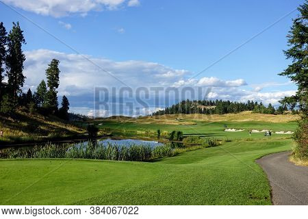 A Beautiful View Of A Par 4 Dog Leg Left From A Tee Box Over A Lake.  It Is A Sunny Day With Forest