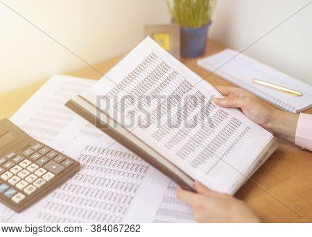 Accountant Or Banker Making Calculations Sitting At Office Table With Documents With Tables On Desk