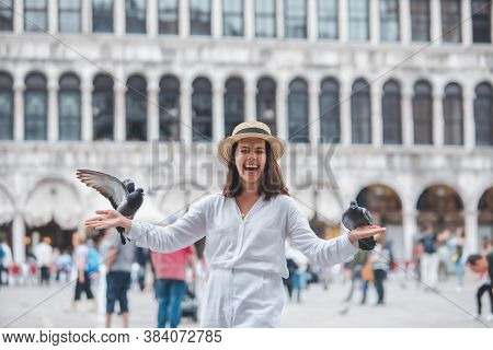 Woman In White Clothes With Straw Hat Having Fun With Pigeons At Venice City Square