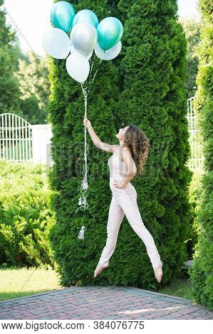 Following Air. Girl With Balloons Celebrate Birthday. Birthday Party. Girl And Bunch Balloons Outdoo
