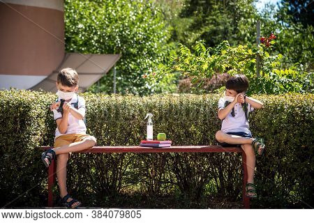 Coronavirus School Reopening Concept: A School Boys Sit On Bench In Front Of A School Wearing A Face