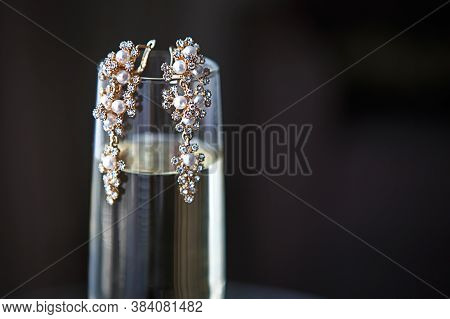Large Gold Earrings With Pearls And Crystals On A Clear Glass Of Champagne. Morning And Gathering Of
