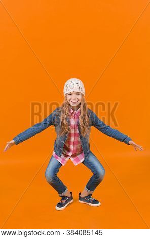 Kid In Jeans Suit, Hat, Plaid Shirt Crouch Smiling On Orange Background. Happy Childhood And Child.