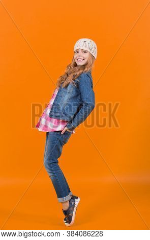 Girl In Jeans Suit, Hat, Plaid Shirt Balance Tiptoe. Child Model With Long Blond Hair Smile On Orang