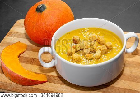 Autumn Pumpkin Soup With Sesame Seeds On A Wooden Background. Pumpkin Soup For Proper Nutrition On A