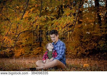 Happy Family Having Fun Outdoor In Autumn Park. Father And Son Against Yellow Blurred Leaves Backgro
