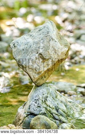 Balanced Rock At The Creek. A Cube Shaped Rock Is Naturally Balanced On Top Of A Rock In A Creek, Wh