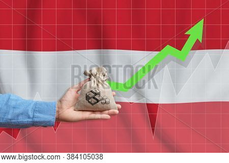The Concept Of Economic Growth In Republic Of Austria. Hand Holds A Bag With Money And An Upward Arr
