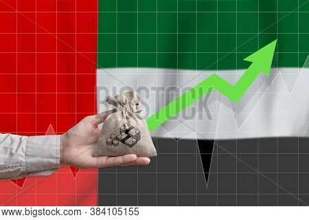 The Concept Of Economic Growth In United Arab Emirates. Hand Holds A Bag With Money And An Upward Ar