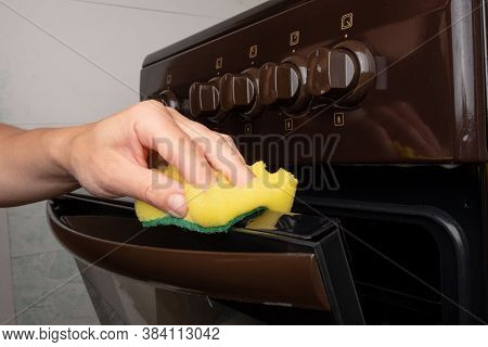 Cleaning The Surface On A Gas Oven With A Yellow Washcloth, Cleaning The Kitchen.