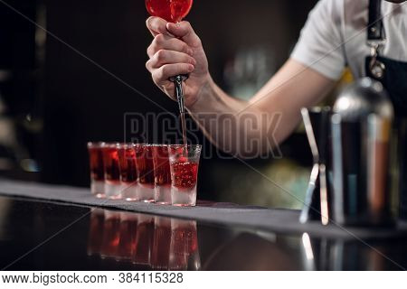 Bartender Pours Red Alcohol Into Shots On The Bar, Bartenders Show.