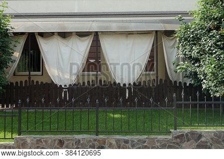 The Facade Of The Summer Veranda Of The Restaurant With Brown Curtains On The Street With Green Gras