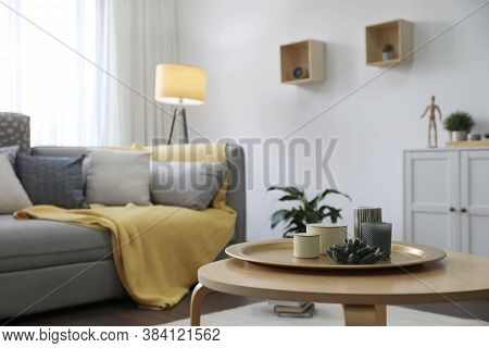 Wooden Table With Candles And Tray Near Sofa In Living Room. Interior Design
