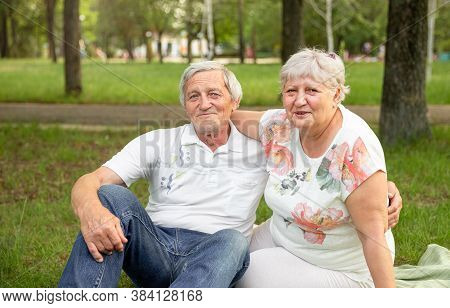 Caucasian Elderly Couples Sit And Relax In The Park. Senior Couple Having Fun And Embracing. Senior