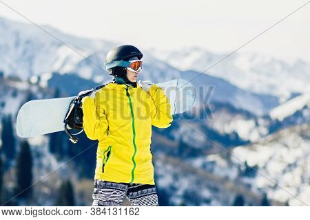 Young Woman Snowboarder With Snowboard On Her Shoulders Looks At The Ski Slope, Copy Space