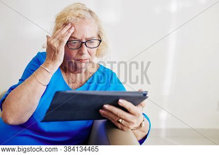 Confused Senior Woman In Glasses Reading Disturbing News On Tablet Computer