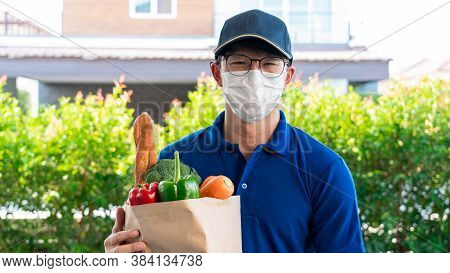Asian Deliver Man In Uniform With Respirator Face Mask Is Delivering The Paper Bag Waiting For The C