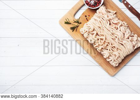 Minced Chicken On A Cutting Board With And Lime. White Table Copy Space.