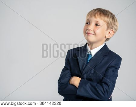 Portrait of white smiling kid in a blue business suit looking away.  Photo of a thinking businessman  boy looking away.  Caucasian boy with a sly look with crossed arms, posing at studio.