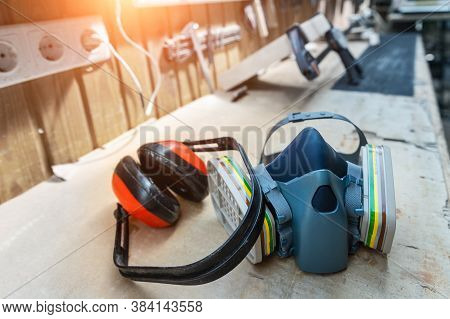 Ppe Respirator Face Half Mask And Ear Protection Equipment On Wooden Workbench Of Carpentry Professi