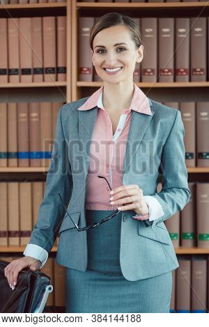 Attorney at law in her office in front of book shelf in the library