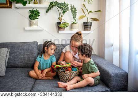 Children Knitting Together, Sitting On Couch In The Home, Cozy Living Room. Apartment Interior With
