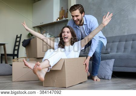 Happy Couple Is Having Fun With Cardboard Boxes In New House At Moving Day, Woman Riding Sitting In