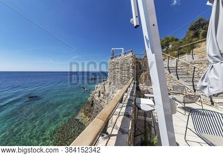 Pula, Croatia - August 25, 2020: View Of The Open Sea And A Girl Jumping From A Rock Into The Sea In