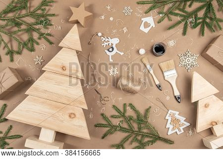 Xmas Or New Year Composition. Wooden Christmas Trees, Paint, Brushes And Fir Branches On Craft Beige