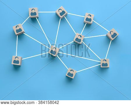Wooden Blocks With People Icon Interconnected By White Lines On Blue Background. Cooperation, Teamwo