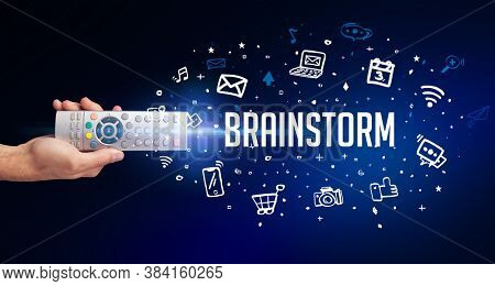 hand holding wireless peripheral with BRAINSTORM inscription, social media concept