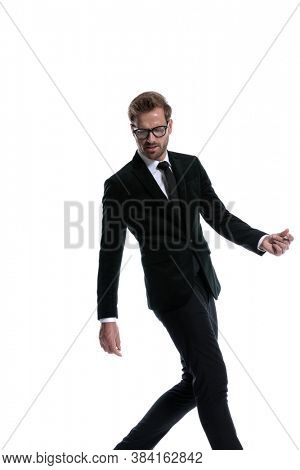 sexy cool young businessman wearing glasses looking down and posing, gesturing and walking isolated on white background