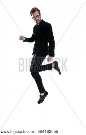side view of frowning cool man in black suit holding knee up, jumping, celebrating, looking down on white background, full body