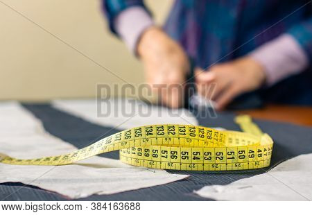 Measuring Tape With Dressmaker Cutting Fabric With Scissors In The Background. Selective Focus On Me