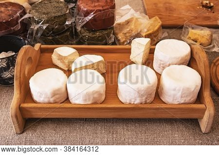 Round Heads Of White Camembert And Brie Cheese On A Wooden Tray Near Packages Of Assorted Craft Chee