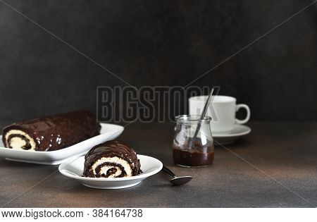 Chocolate Roll With Cream Cheese And Coffee On Dark Background