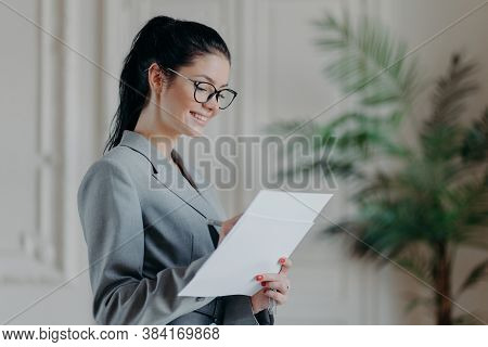 Glad Female Lawyer Writes In Corporate Paper Documents, Wears Optical Glasses, Formal Clothes, Stand