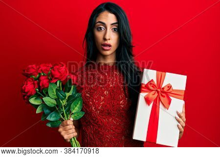 Beautiful hispanic woman holding anniversary gift and roses bouquet in shock face, looking skeptical and sarcastic, surprised with open mouth