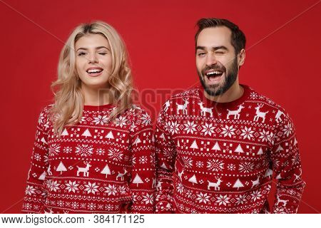 Cheerful Young Couple Guy Girl In Christmas Knitted Sweaters Posing Isolated On Red Background Studi