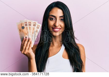 Beautiful hispanic woman holding united kingdom 10 pounds looking positive and happy standing and smiling with a confident smile showing teeth