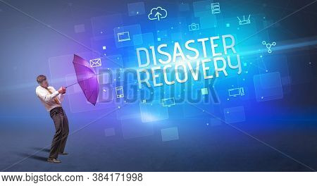 Businessman defending with umbrella from cyber attack and DISASTER RECOVERY inscription, online security concept
